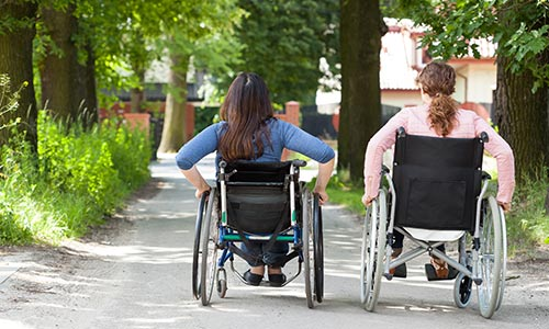 Two women in wheelchairs moving away from the viewer.